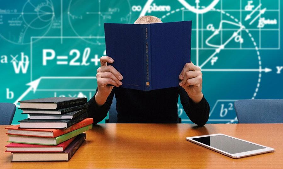 Studierender am Schreibtisch beim Lesen mit Tafel im Hintergrund (Bild: https://pixabay.com/de/schule-studium-lernen-b%C3%BCcher-lesen-2051712/)
