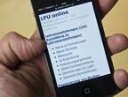 Hand hält Smartphone, auf dem Smartphone ist Mobilversion von LFU:online geöffnet