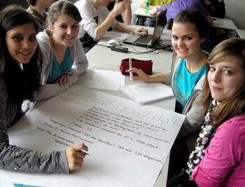 Schülerinnen beim Entwerfen eines Plakats