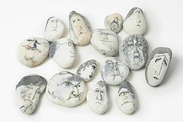 Der zeichnende Paul Flora (© Horst Munzig) und Steine mit gezeichneten Gesichtern aus Floras Atelier (© TLM)