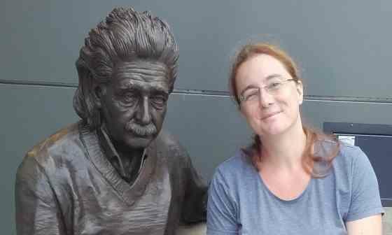 Prof. Schuster sitting next to a statue of Albert Einstein