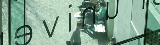 Studierende hinter Glas