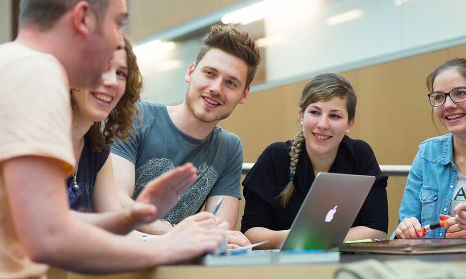 Studierende sitzen vor einem Laptop