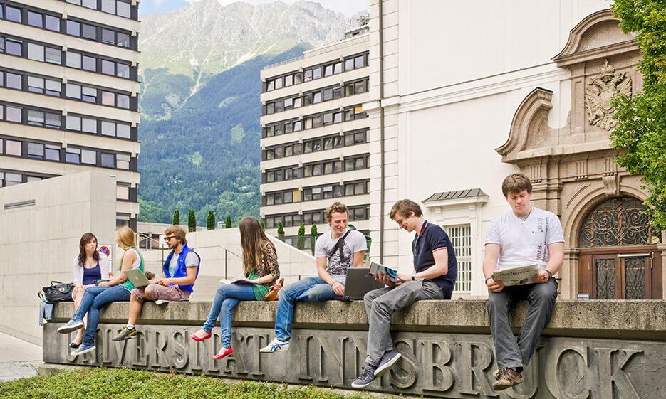 Studierende sitzen auf Mauer