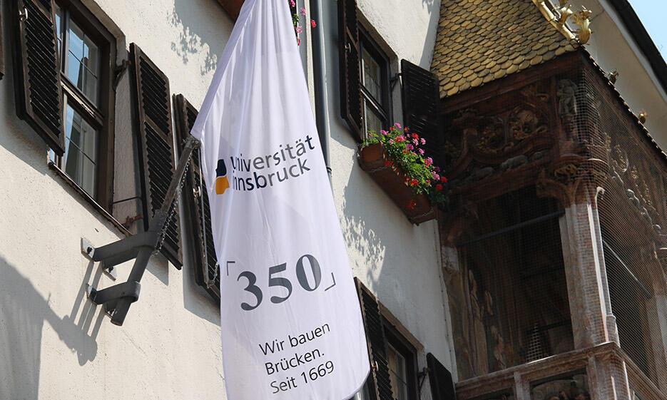 Weiße Fahne mit Universitätslogo und Slogan: 350 - Wir bauen Brücken. Seit 1669